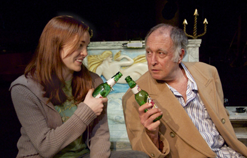"""Katherine Bourne and Fred Curchack build camaraderie as they drink complementary beers in the Neptune Hotel in Undermain Theatre's production of Abraham Zobell's Home Movie: Final Reel..."""" written by Len Jenkin."""