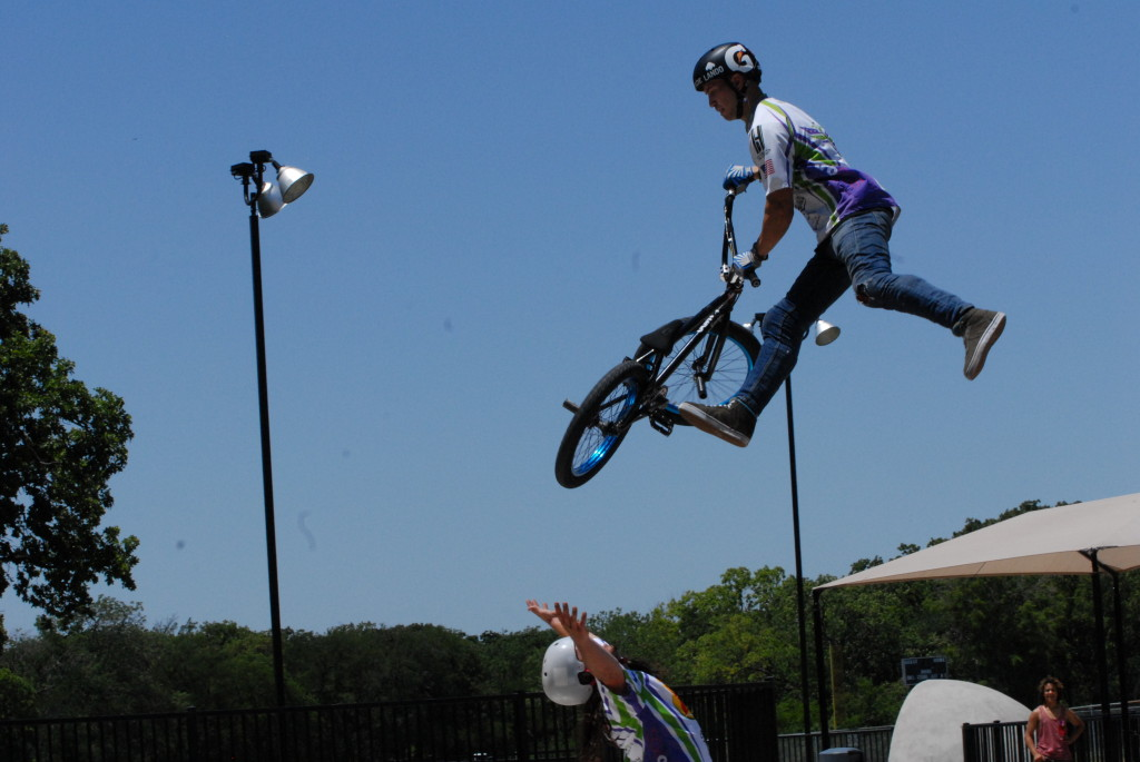 Flying high, Spencer  Bass jumps his bicycle  over his friend, Matt Olson, during a BMX show by Big-Time  Action Sports performed for the Bike  Irving event. / Photo by  John Starkey